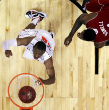 Virginia forward Akil Mitchell (25) scores past North Carolina State forward Richard Howell (1) during the second half of an NCAA college basketball game in the quarterfinals of the Atlantic Coast Conference tournament, Friday, March 9, 2012, in Atlanta. North Carolina State won 67-64. (AP Photo/Chuck Burton)