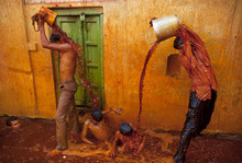 Indian Hindu devotees pour colored water on themselves and each other after taking part in