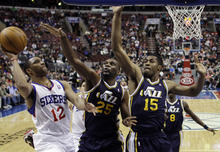 Philadelphia 76ers' Evan Turner (12) goes up for a shot against Utah Jazz's Al Jefferson (25) and Derrick Favors (15) in the first half of an NBA basketball game on Friday, March 9, 2012, in Philadelphia. (AP Photo/Matt Slocum)