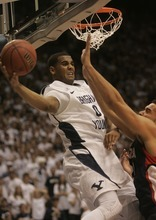 Kim Raff |The Salt Lake Tribune BYU player Brandon Davies passes around the arms of Gonzaga player Elias Harris during the first half of a game at the Marriott Center in Provo, Utah on February 2, 2012.