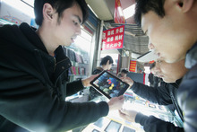In this March 4, 2012 photo, a sales clerk shows a customers a counterfeit iPad-like device at a shop in Shanghai, China. Apple's troubles in China over the iPad trademark are not its first, and given its penchant for