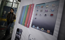 In this March 2, 2012 photo, a man walks past an advertisement of Apple's iPad in Shanghai, China. Apple's troubles in China over the iPad trademark are not its first, and given its penchant for