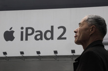 A man stands near an advertisement of Apple's iPad  in Shanghai, China, Tuesday March 6, 2012. A major creditor of Proview Electronics, which is challenging Apple Inc.'s use of the iPad trademark, has moved to have the ailing computer monitor maker liquidated, Chinese media reports said. (AP Photo/Eugene Hoshiko)