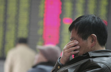 An investor rub his eyes at a private securities company in Shanghai, China, Tuesday March 6, 2012. Asian stock markets slid Tuesday over worries about slower economic growth in China and a possible snag in the deal for Greece to get its bailout money. Mainland China's Shanghai Composite Index fell 1 percent to 2,417.29. (AP Photo)