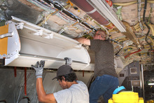 Photo provided by AMR Workers instal larger bins for carry-on luggage on a Boeing 737, in Tulsa, Okla. Fliers can stop sharpening their elbows. Overhead bins are getting bigger.