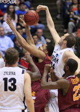 Brigham Young forward Noah Hartsock (34) blocks a shot by Iona forward Mike Glover in the first half of an NCAA men's college basketball tournament opening-round game, Tuesday, March 13, 2012, in Dayton, Ohio. (AP Photo/Al Behrman)