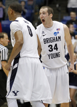 Brigham Young forward Noah Hartsock (34) celebrates with forward Brandon Davies (0) in the closing seconds of BYU's 78-72 win over Iona in an NCAA men's college basketball tournament opening-round game, Tuesday, March 13, 2012, in Dayton, Ohio. Hartsock led Brigham Young with 23 points and Davies added 18. (AP Photo/Skip Peterson)