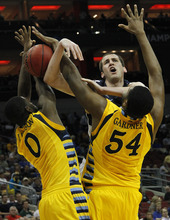 Marquette forward Davante Gardner (54) and Marquette forward Jamil Wilson (0) block the shot of BYU forward Noah Hartsock (34) in the second half of their NCAA tournament second-round college basketball game in Louisville, Ky., Thursday, March 15, 2012. (AP Photo/Dave Martin)