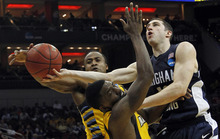 BYU guard Matt Carlino, right, drives the lane as Marquette guard Darius Johnson-Odom, front, and Marquette guard Junior Cadougan, left, defend in the second half of their NCAA tournament second-round college basketball game in Louisville, Ky., Thursday, March 15, 2012. (AP Photo/Dave Martin)