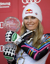 Lindsey Vonn, of the United States, shows the trophy of the alpine ski, women's World Cup super-G discipline title, in Schladming, Austria, Thursday, March 15, 2012. (AP Photo/Alessandro Trovati)