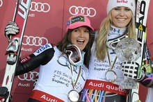 Lindsey Vonn of the US, right, celebrates with the crystal globe of the winner of the Super G World Cup celebrates with second placed compatriot Julia Mancuso on the podium of the alpine skiing World Cup, in Schladming, Austria, Thursday, March 15, 2012. (AP Photo/Keystone, Jean-Christophe Bott)