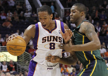 Phoenix Suns' Channing Frye (8) collides with Utah Jazz's Derrick Favors in the first quarter of an NBA basketball game, Wednesday, March 14, 2012, in Phoenix.(AP Photo/Ross D. Franklin)
