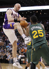 Phoenix Suns' Marcin Gortat, left, of Poland, battles Utah Jazz's Al Jefferson (25) for a rebound in the first quarter of an NBA basketball game, Wednesday, March 14, 2012, in Phoenix.(AP Photo/Ross D. Franklin)