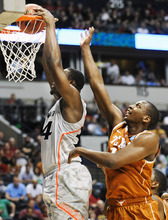 Donn Jones | The Associated Press Cincinnati forward Yancy Gates, left, dunks the ball ahead of Texas forward Jonathan Holmes, right, in the first half of a second-round NCAA college basketball tournament game on Friday, March 16, 2012, in Nashville, Tenn. (AP Photo/Donn Jones)