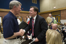 Kim Raff | The Salt Lake Tribune Dan Liljenquist talks with Ray Westergard at the Republican caucuses at Mueller Park Jr. High in Bountiful on Thursday.