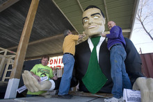 Paul Fraughton | The Salt Lake Tribune. Following in the tradition of poking fun at the establishment, Matt Ivers, Vince Coley and Leonard Mascher, work on their float for the St. Patrick's Day Parade, an oversized effigy of Mitt Romney with dollar signs for eyes clutching giant 100 dollar bills. The float will be towed by a truck driven by  the  infamous family dog with Mitt himself in a cage in the truck's bed.  Thursday, March 15, 2012