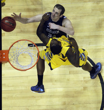 Brigham Young forward Noah Hartsock (34) shoots over the defense of Marquette guard Derrick Wilson (33) in the second half of their NCAA tournament second-round college basketball game in Louisville, Ky., Thursday, March 15, 2012. Marquette beat BYU 88-68. (AP Photo/Dave Martin)