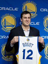 Newly acquired Golden State Warriors center Andrew Bogut, of Australia, poses with his new jersey during a news conference, Friday, March 16, 2012, in Oakland, Calif. The Warriors acquired Bogut from the Milwaukee Bucks. (AP Photo/Ben Margot)