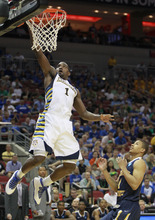 Marquette guard Darius Johnson-Odom (1) dunks the ball over Murray State forward Stacy Wilson in the first half of their NCAA third-round tournament college basketball game in Louisville, Ky., Saturday, March 17, 2012. (AP Photo/John Bazemore)