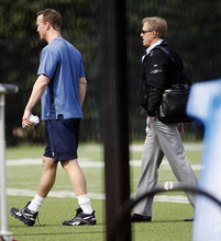 NFL quarterback Peyton Manning, left, walks across a football practice field with Denver Broncos executive John Elway, right, near Wallace Wade Stadium, Friday, March 16, 2012, at Duke University in Durham, N.C. Elway and coach John Fox watched the star quarterback throw at Duke's athletic fields. (AP Photo/The News & Observer, Travis Long)