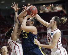 Michigan guard Carmen Reynolds (33) is fouled by Oklahoma guard Whitney Hand, right, as she shoots between Hand and forward Kaylon Williams, left, in the second half of an NCAA tournament first-round women's college basketball game in Norman, Okla., Sunday, March 18, 2012. Oklahoma won 88-67. (AP Photo/Sue Ogrocki)