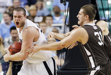 Xavier's Kenny Frease pulls down a rebound over Lehigh's Justin Maneri (31) during the second half of an NCAA tournament third-round college basketball game in Greensboro, N.C., Sunday, March 18, 2012. Xavier won 70-58. (AP Photo/Gerry Broome)