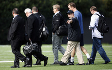 NFL quarterback Peyton Manning, second from right at rear, walks across a football practice field with Denver Broncos executive John Elway, fourth from left, near Wallace Wade Stadium, Friday, March 16, 2012, at Duke University in Durham, N.C. Elway and coach John Fox watched the star quarterback throw at Duke's athletic fields. (AP Photo/The News & Observer, Travis Long)