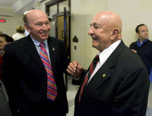 Tribune file photo Retired state Sen. Mike Dmitrich, right, chats outside the state Senate chambers. Dmitrich is one of a large cadre of former lawmakers who return to Capitol Hill as lobbyists.