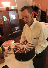 Francisco Kjolseth  |  The Salt Lake Tribune Scott Sorensen prepares a slice of five-layer chocolate cake at Lamb's Grill Cafe, which has a new owner and chef. Many of the well-known dishes remain on the menu, including the lamb shank, braised for five hours at 300 degrees.