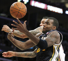 Utah Jazz forward Paul Millsap, right, pulls down a rebound against Los Angeles Lakers forward Matt Barnes during the second half of an NBA basketball game in Los Angeles, Sunday, March 18, 2012. The Jazz won 103-99. (AP Photo/Alex Gallardo)