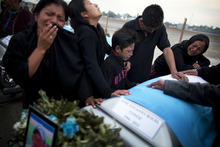 Relatives mourn next to the coffin of Guatemalan citizen Jose Yovanny Bocel, at an Air Force base in Guatemala City, Wednesday, March 21, 2012. The bodies of 11 Guatemalan citizens were repatriated from Mexico Wednesday,  part of 72  migrants from  South and Central America killed, according to Mexican authorities, by the Zetas drug cartel August 2010 in the northeastern Mexico town of San Fernando, just 100 miles from the U.S. border.(AP Photo/Rodrigo Abd)