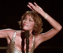 In this April 10, 2000 file photo, entertainer Whitney Houston strikes a pose during her performance at the Shrine Auditorium in Los Angeles during taping of the