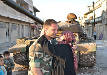 In this picture taken on Wednesday, March 21, 2012, a Syrian woman, right, kisses a soldier from the Free Syrian Army, left, in front a destroyed Syrian army forces tank which was attacked during clashes between the Syrian government forces and the Syrian rebels, in Rastan town in Homs province, central Syria. Syrian government forces fired machine guns and mortar rounds Friday in fierce clashes with rebel army defectors in a town near the Turkish border, a Syrian activist group reported, as a European Union official said the wife of Syria's president will be hit with a travel ban and have her assets in the EU frozen. (AP Photo)