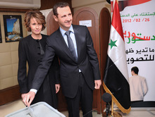 FILE - In this Feb. 26, 2012 file photo provided by the Syrian official news agency SANA, Syrian President Bashar Assad casts his ballot next to his wife Asma at a polling station in Damascus, Syria, during a referendum on the new constitution. EU foreign ministers imposed sanctions Friday, March 23, 2012 on Asma Assad, the stylish, British-born wife of the Syrian president, banning her from traveling to European Union countries and freezing any assets she may have there. The foreign ministers also imposed the same sanctions on President Bashar Assad's mother, sister and sister-in-law, and eight government ministers, in a continuing attempt to stop the bloody crackdown on opposition in the country. (AP Photo/SANA, File)