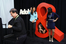 Francisco Kjolseth  |  The Salt Lake Tribune Photographer Rikk Flohr gets ready on Wednesday to take a picture of Adobe Digital employees Jennifer Sun, left, Ramona Meyer-Piagentini and Kripa Sethumadhavan by the oversized Adobe symbol. Adobe Systems is holding one of the world's largest digital marketing conferences in the world as 4,000 people descend on the Calvin L. Rampton Salt Palace Convention Center in Salt Lake City.