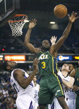 Utah Jazz forward DeMarre Carroll (3) battles for a rebound against Sacramento Kings defenders Tyreke Evans, left, and Jimmer Fredette, right, during the first half of an NBA basketball game in Sacramento, Calif., Thursday, March 22, 2012. (AP Photo/Steve Yeater)
