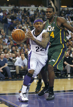 Sacramento Kings guard Isaiah Thomas, left, drives the lane against Utah Jazz defender Paul Milsap during the second half of an NBA basketball game in Sacramento, Calif., Thursday, March 22, 2012. The Jazz won 103-102.(AP Photo/Steve Yeater)