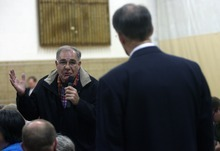 Kim Raff | The Salt Lake Tribune (left) Duane Call asks stern questions of MTC director Richard Heaton during a neighborhood meeting at Rock Canyon Elementary School in Provo to discuss building a new nine-story MTC building on March 22, 2012.
