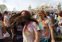 Francisco Kjolseth  |  The Salt Lake Tribune Revelers dance to the music as they throw bright colorful chalk made of edible maize during Holi, the Festival of Colors at Sri Radha Krishna Temple in Spanish Fork on Saturday, March 24, 2012. Thousands packed the temple grounds to celebrate Holi, the traditional Indian announcement of the arrival of spring and the passing of winter. The festival continues Sunday.