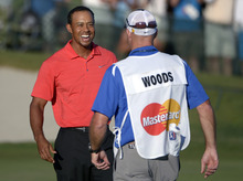 Tiger Woods, left, celebrates with his caddie Joe LaCava after winning the Arnold Palmer Invitational golf tournament at Bay Hill in Orlando, Fla., Sunday, March 25, 2012. (AP Photo/Phelan M. Ebenhack)
