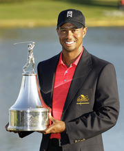 Tiger Woods holds up the championship trophy after winning the Arnold Palmer Invitational golf tournament at Bay Hill, Sunday, March 25, 2012, in Orlando, Fla. (AP Photo/John Raoux)