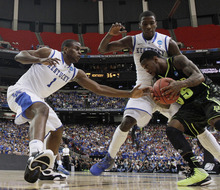 Baylor's Pierre Jackson (55) drives against Kentucky's Michael Kidd-Gilchrist, center, and Kentucky's Darius Miller during the first half of an NCAA tournament South Regional finals college basketball game Sunday, March 25, 2012, in Atlanta. (AP Photo/John Bazemore)