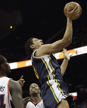 Utah Jazz's Enes Kanter, right puts up a shot past Atlanta Hawks' Jason Collins, rear, and Marvin Williams, left, during the second quarter of an NBA basketball game Sunday, March 25, 2012, in Atlanta. (AP Photo/David Goldman)