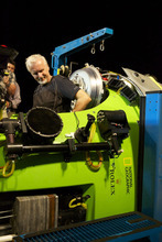 In this photo provided by National Geographic, filmmaker and National Geographic Explorer-in-Residence James Cameron slides into the hatch of the DEEPSEA CHALLENGER submersible as he prepares for his record dive to the bottom of the Mariana Trench, Sunday, March 25, 2012. The dive was part of DEEPSEA CHALLENGE, a joint scientific expedition by Cameron, the National Geographic Society and Rolex to conduct deep-ocean research. (AP Photo/National Geographic, Mark Thiessen) MANDATORY CREDIT