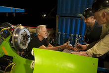 In this photo provided by National Geographic, filmmaker and National Geographic Explorer-in-Residence James Cameron gets a handshake from ocean explorer and U.S. Navy Capt. Don Walsh, right, just before the hatch on the DEEPSEA CHALLENGER submersible is closed and the voyage to the deepest part of the ocean begins, Sunday, March 25, 2012. Walsh took the same journey to the bottom of the Mariana Trench 52 years ago in the bathyscaphe Trieste with Swiss oceanographer Jacques Piccard. Cameron is the first person to complete the dive solo. The dive was part of DEEPSEA CHALLENGE, a joint scientific expedition by Cameron, the National Geographic Society and Rolex to conduct deep-ocean research. (AP Photo/National Geographic, Mark Thiessen) MANDATORY CREDIT