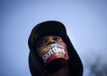 Jajuan Kelley, of Atlanta, wears a Skittles wrapper over his mouth during a rally in memory of Trayvon Martin, the unarmed 17-year-old who was killed by a Florida neighborhood watch captain while returning from a convenience store with a bag of Skittles and an iced tea, Monday, March 26, 2012, in Atlanta. (AP Photo/David Goldman)