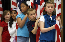 Francisco Kjolseth  |  The Salt Lake Tribune Third-graders at Falcon Ridge Elementary Emily Hewitt, 8, Madeline Leano, 9, Pisila Fangupo, 9, Jack Anderson, 8, and Eve Benedict, 8, from left, get ready for a flag presentation where Governor Gary R. Herbert signed into law three education-related bills at at the school in West Jordan on Tuesday, March 27, 2012.