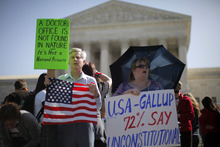 David Hayes, from Washington, left, and Maureen Murphy from Madison, Miss., who oppose the health care reform law signed by President Barack Obama, rally in front of the Supreme Court in Washington, Monday, March 26, 2012, as the court begins three days of arguments on health care. (AP Photo/Charles Dharapak)
