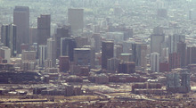 The skyline of downtown Denver is occluded by smoke from the Lower North Fork Wildfire burning in the foothills community of Conifer, Colo., southwest of Denver on Tuesday, March 27, 2012. Firefighters are now able to actively battle the blaze on the ground that started on Monday and has already destroyed at least 16 homes in the rugged terrain. (AP Photo/David Zalubowski)