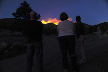Residents watch as a wildfire threatens to come over a ridge near Reynolds Park on Foxton Road in Conifer, Colo., Monday, March 26, 2012.  A wildfire erupted amid dry, windy weather in Colorado on Monday, and authorities say at least some homes were destroyed in the mountains west of Denver. (AP Photo/The Denver Post, Helen H. Richardson)